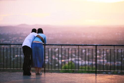 #PraCegoVer: Casal assistindo ao nascer do sol.