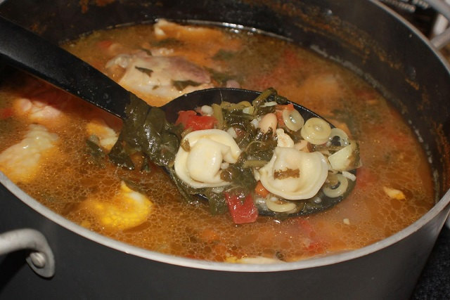 a big soup pot with vegetables, spinach tortellini pasta and rich chicken broth