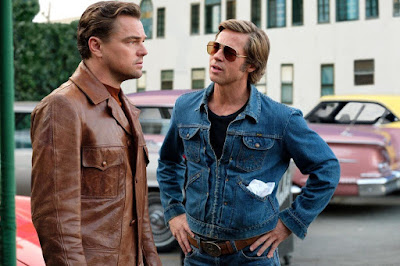 Movie still for Quentin Tarantino's 2019 film Once Upon a Time in Hollywood where Leonardo DiCaprio and Brad Pitt talk to each other in a parking lot
