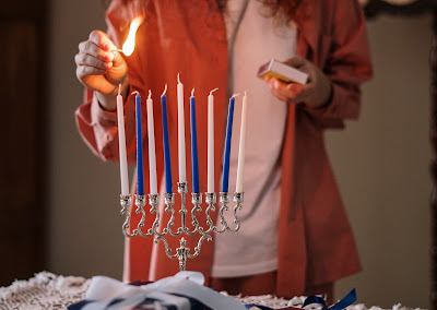 woman lighting a Chanukah menorah