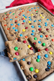first piece of chewy salted caramel M&M blondies being lifted out of sheet pan with spatula