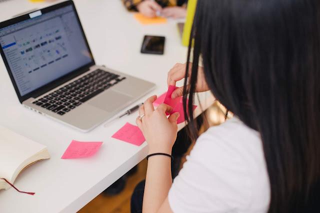 Menina em frente ao computador organizando post-its rosa