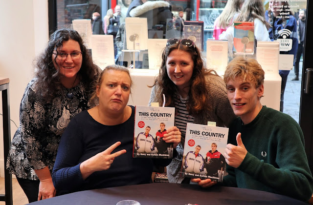 Myself and Jade standing behind Daisy May Cooper and Charlie Cooper  who are holding copies of their new book. Daisy May is holding two fingers up to the camera