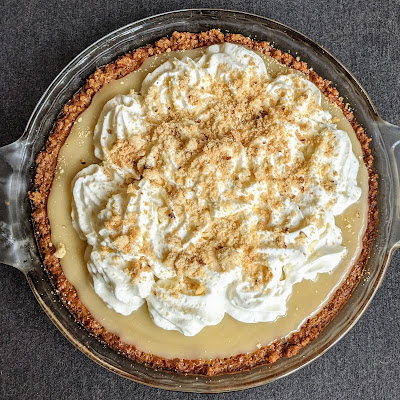 Overhead shot of a caramel custard pie, toppied with whipped cream and cookie crumbles