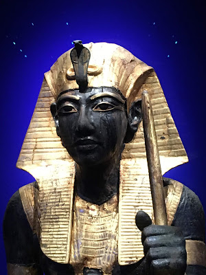 head and shoulders photo of statue of  Tutankhamun in black wood with gold headdress