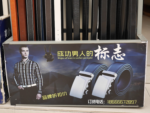 "sign for belts for sale with a black rabbit logo and ""Sign of successful people"""