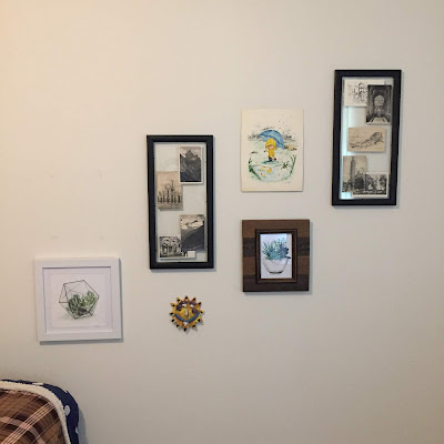 A photo of a gallery wall in a grad student apartment bedroom, including framed pictures