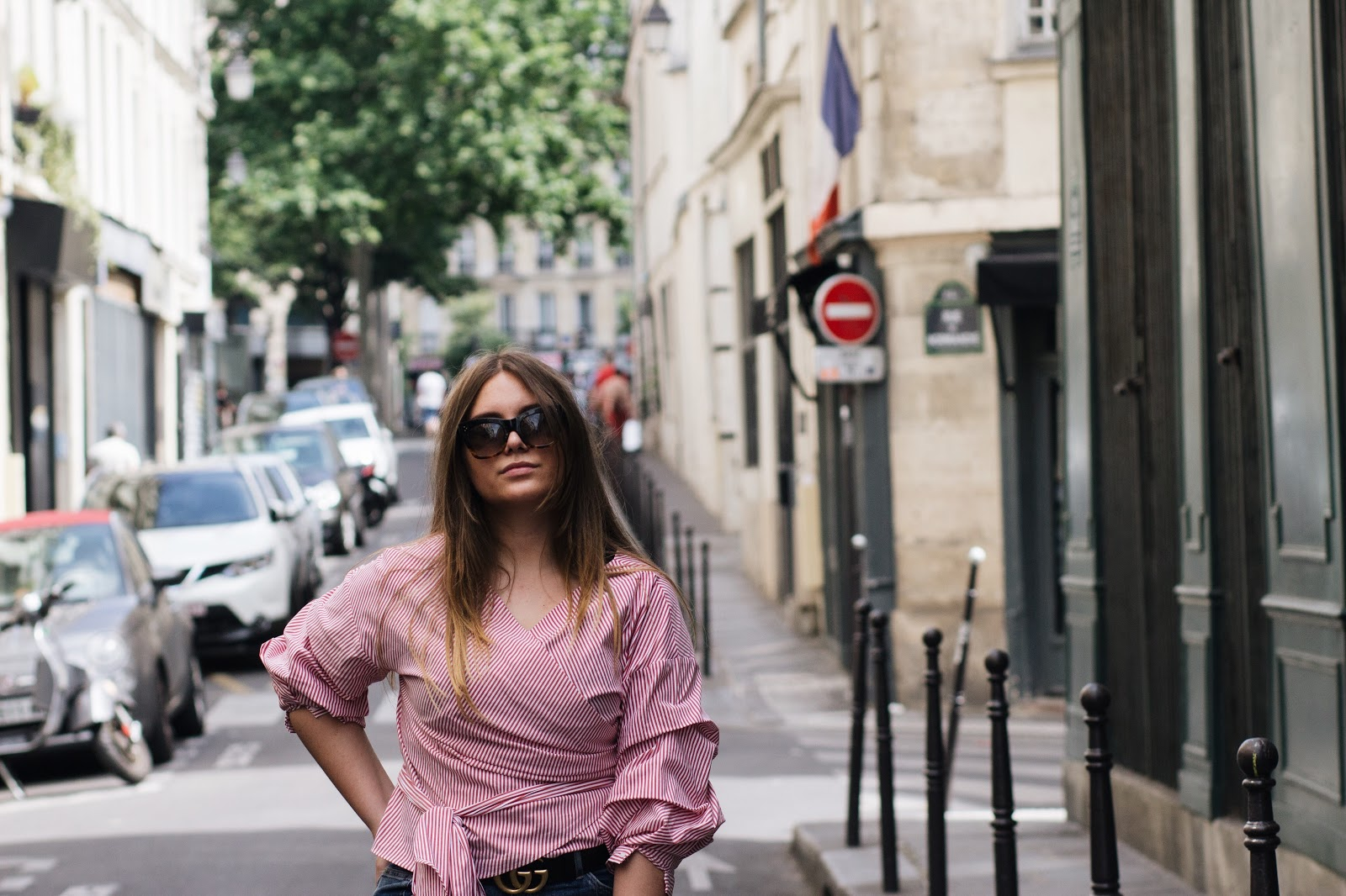 blogger dominique candido wearing a zara shirt h&m jeans alexander mcqueen sneakers celine sunglasses and a balanciaga bag in paris
