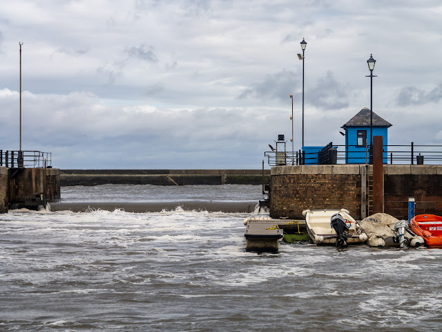 Photo of water pouring over the closed sea gate at Maryport Marina on Saturday