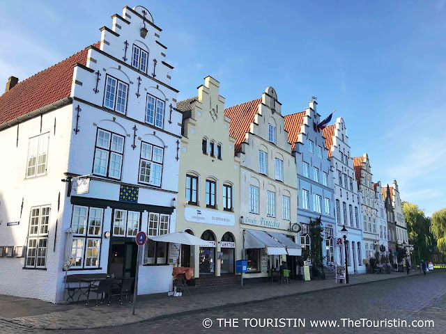 Nine gabled merchant houses line a cobblestone street, under a blue sky.
