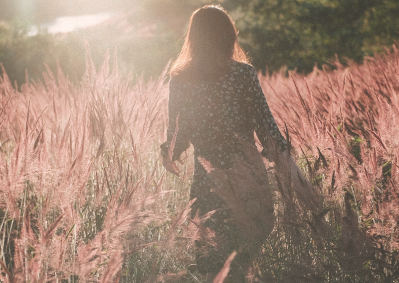 Lady walking through a field in a post about 15 easy self-care ideas you can start today.