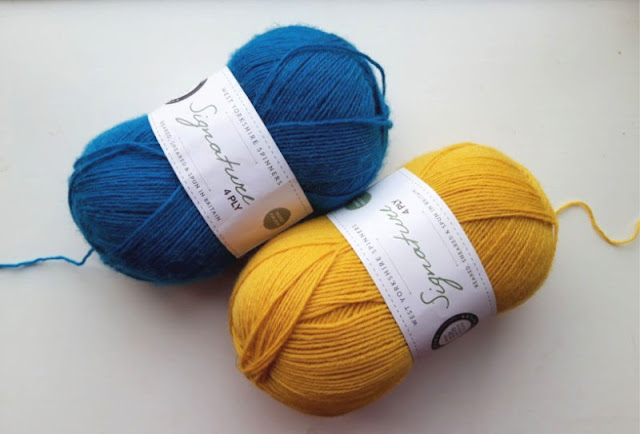 Image shows two balls of WYS Signature 4ply yarn on a white background.  To the left is Blueberry Bon Bon and to the right is Butterscotch (yellow)