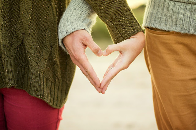 holding hands in heart shape.Photo by Anthony Intraversato on Unsplash