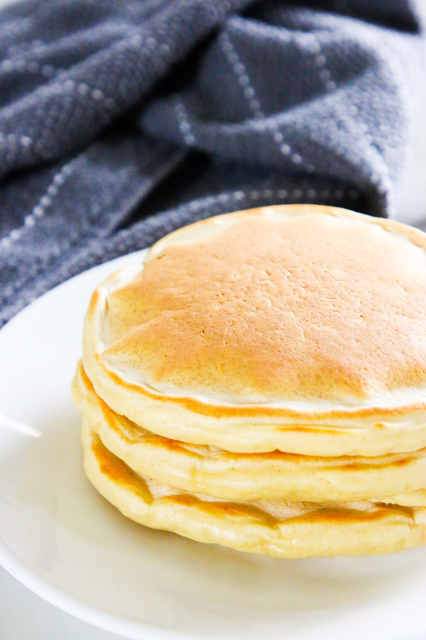 A stack of three pancakes on a plate with a fork and drizzle of syrup