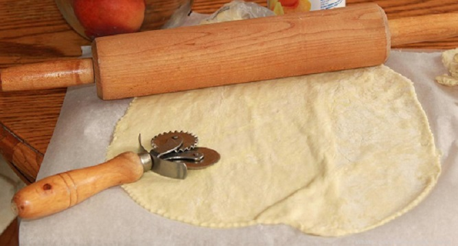 this is homemade dough with a rolling pin on a cutting board that will be filled with apple pie filling and air fried
