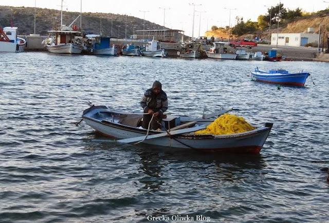 rybaczka zwija cumę, kobieta w chustce na łódce niebieska łódka limenas port grecja chios