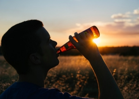 A man drinking beer at sunset.