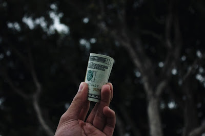 A person's hand holding up a roll of dollar bills