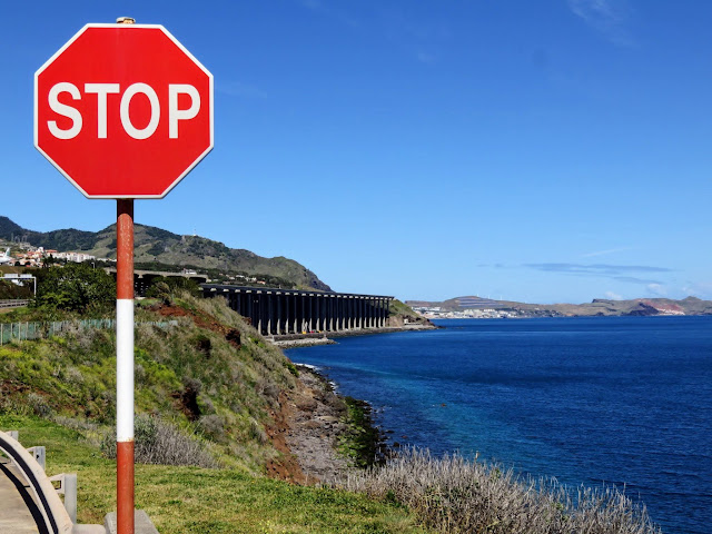 Stop sign with view of Funchal airport runway on stilts behind it in Madeira