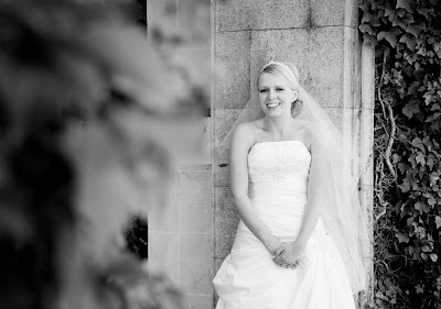 Blonde bride against a castle wall on her wedding day
