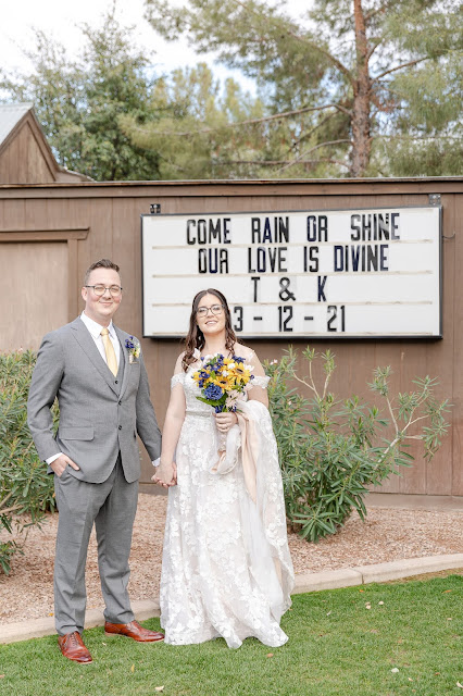 bride and groom posing in front of a marquee board