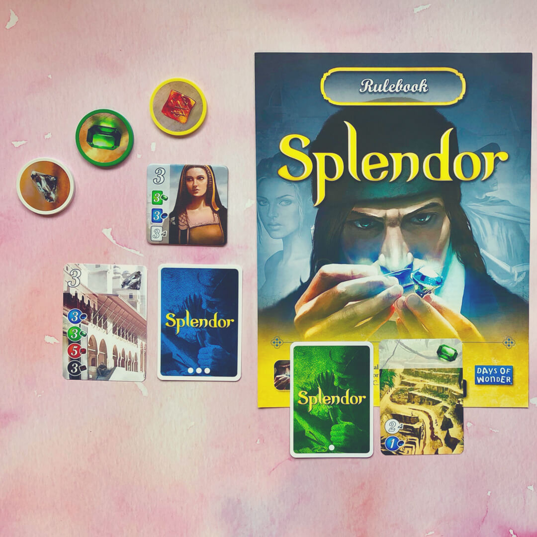 Splendor - the board game - cards, tokens, and rulebook set on a pink background.