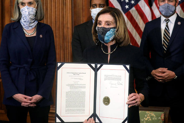 House Speaker Nancy Pelosi shows the article of impeachment against Donald Trump after she signed it on January 13, 2021.