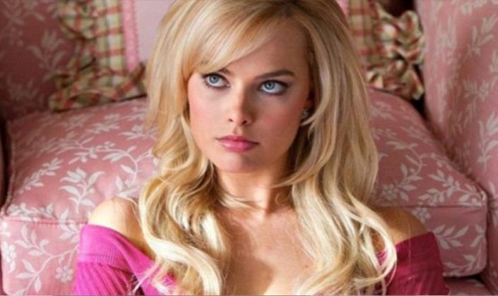 Imagem de capa: a atriz Margot Robbie, uma mulher branca com cabelos loiros, olhos azuis e um batom rosa, em uma roupa rosa e encostada em uma cama rosa com detalhes brancos de uma cena de um filme, porém parecendo muito com a Barbie.