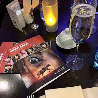 Bradford Alhambra theatre brochures and a glass of prosecco on a restaurant table