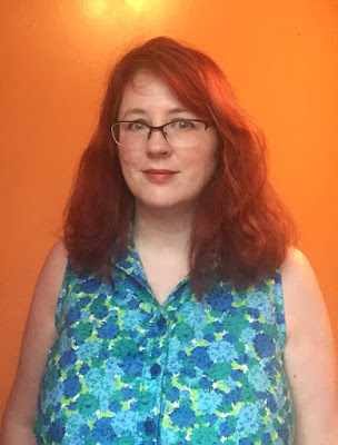 A redheaded woman in a blue and green floral top against an orange background. The woman is looking into the camera and smiling.