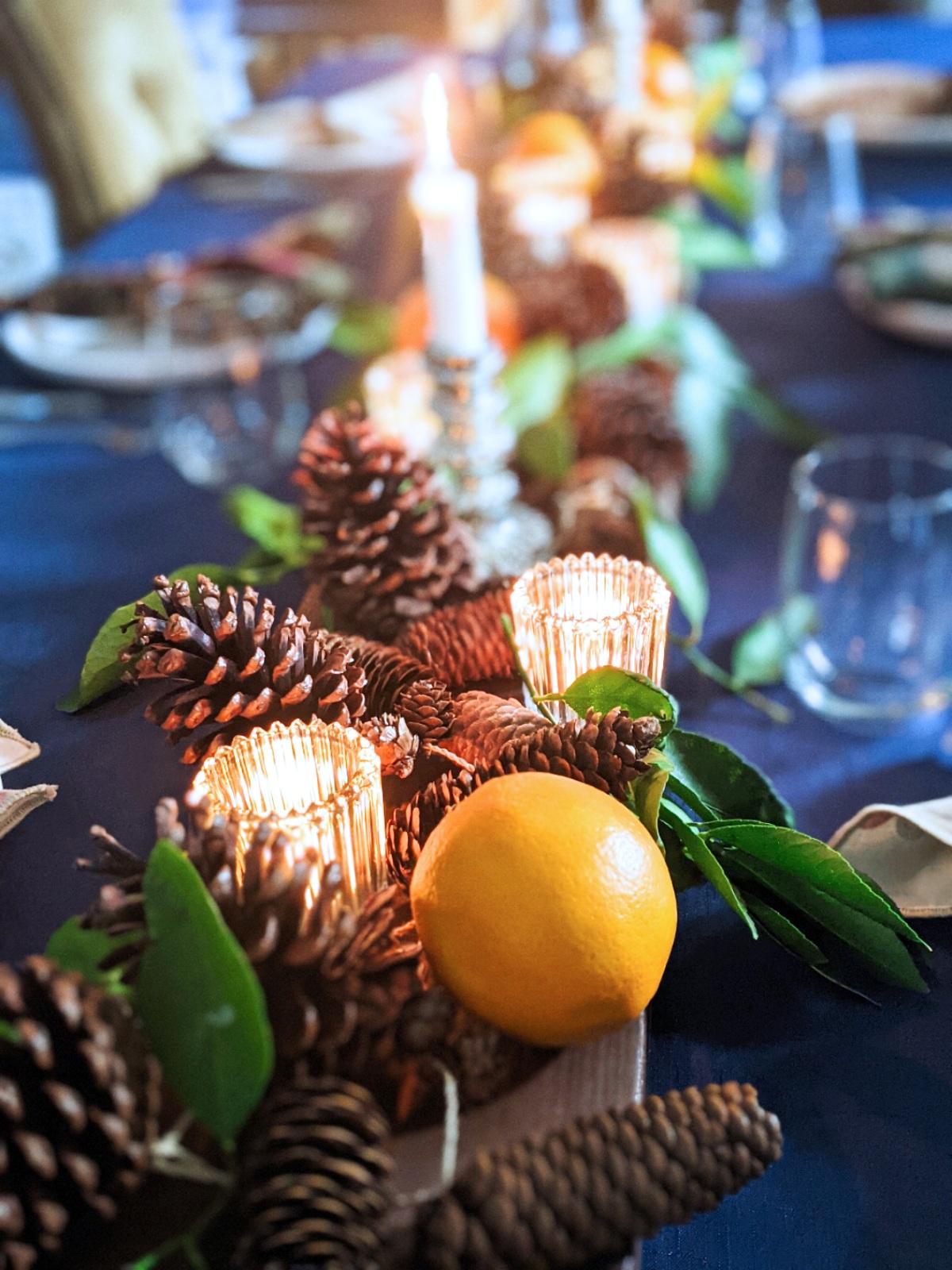 CAD Interiors dining table setting holidays fruit lemons pinecones pine garland candles natural