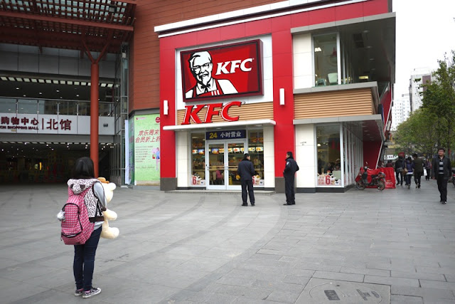 girl hold stuffed bear appearing to look at a KFC