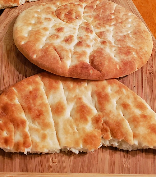 pita bread on a wooden board getting ready to make into pizza