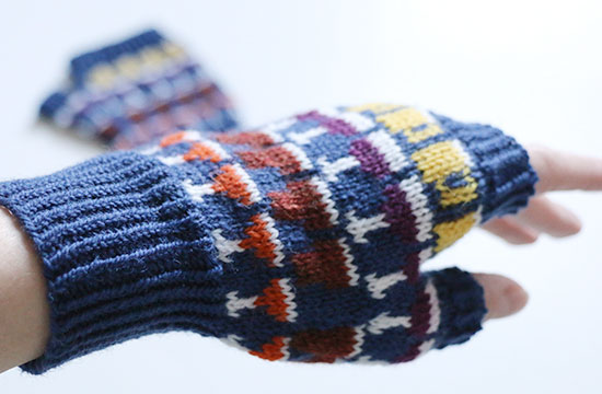 Back of hand wearing knit colorwork Drinkers Mitt in blue with details in white, yellow, purple, brown and orange with second mitt out of focus on a white background.