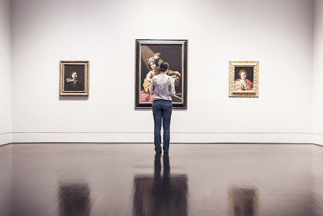 Girl in art gallery looking at painting