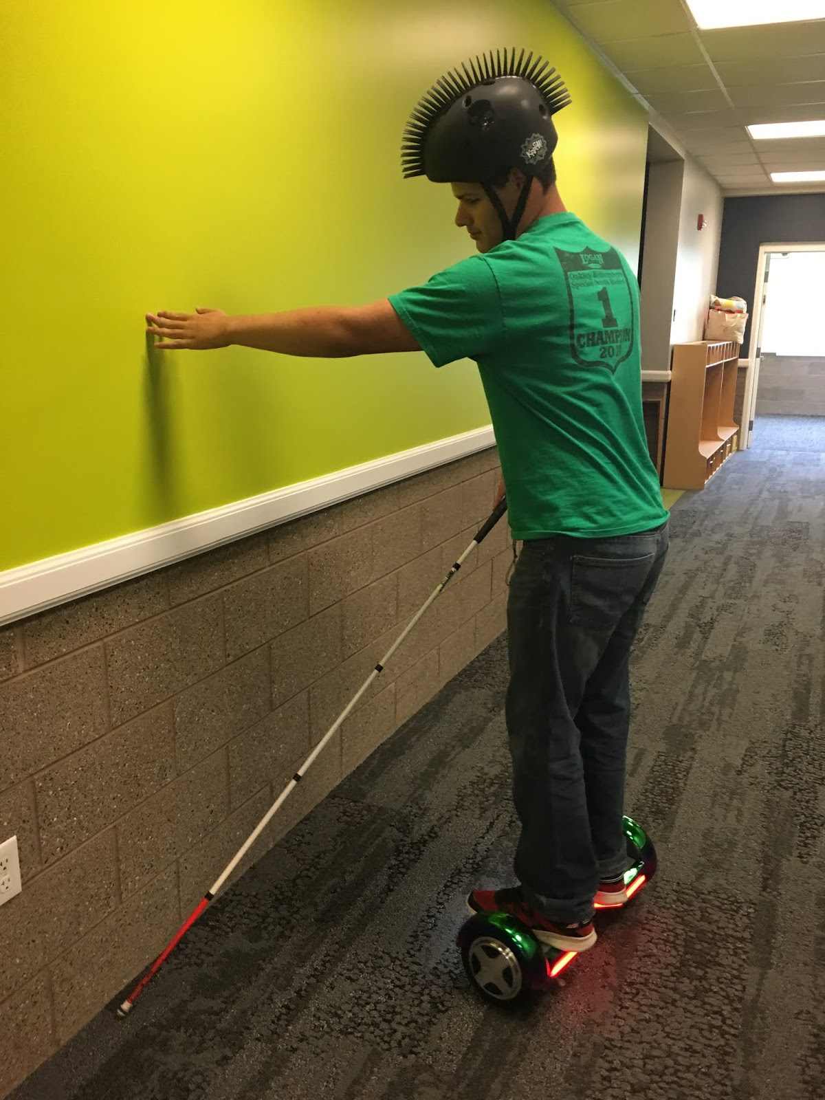 a male teenager moves on the hoverboard and uses his cane
