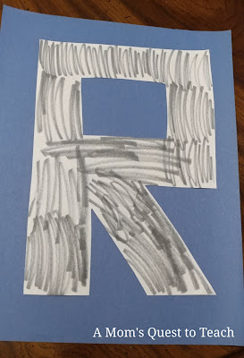 letter R colored gray on blue construction paper background