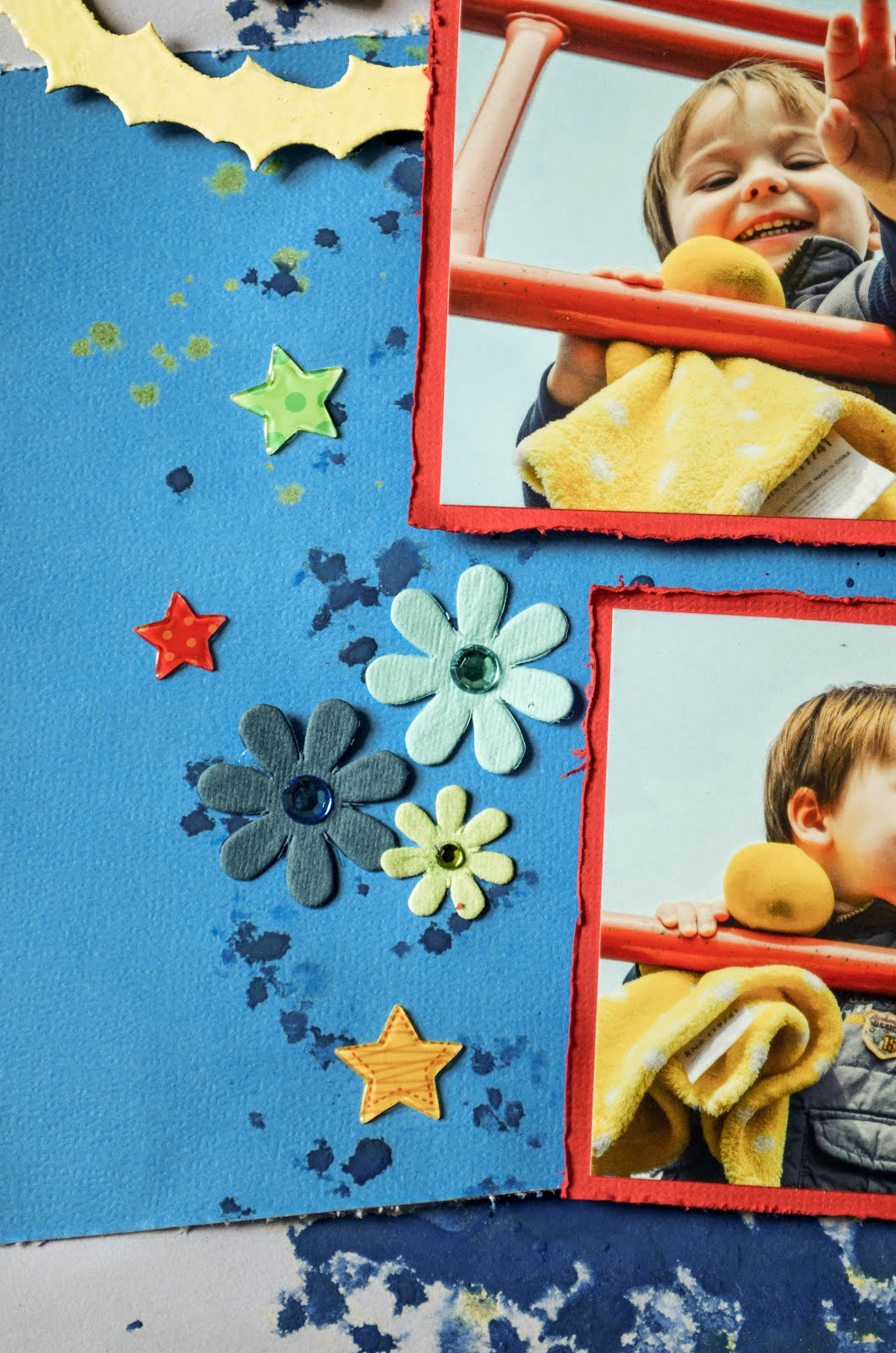 Boy scrapbook layout in primary colors (red, blue, yellow) with acrylic paint, embossed chipboard sun, and flowers with glittery hearts and flowers