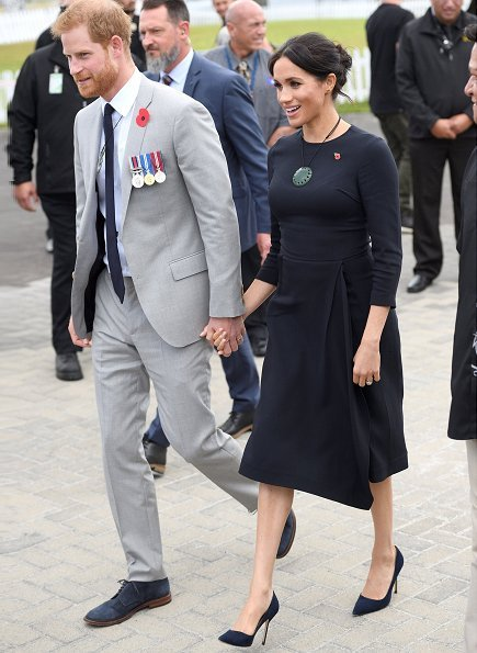 Duchess of Sussex wore Stella McCartney navy asymmetric crêpe dress. Kiri nathan Pounamu Kouma, carved by Jason Nathan