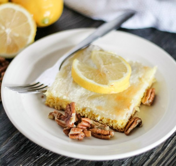 pice of lemon cake bar with cream cheese and pecan topping and lemon slices
