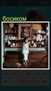 маленькая девочка стоит около стены с игрушками босиком 21 уровень 667 слов