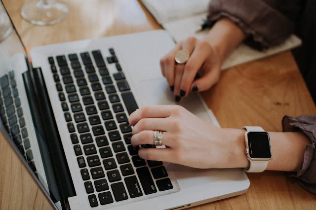 Mãos de mulher sobre o teclado de um computador portátil