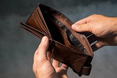 Foto imagem de uma mão segurando uma carteira de couro marrom aberta e vazia ilustrando artigo sobre a lei que suspendeu despejos em 2021