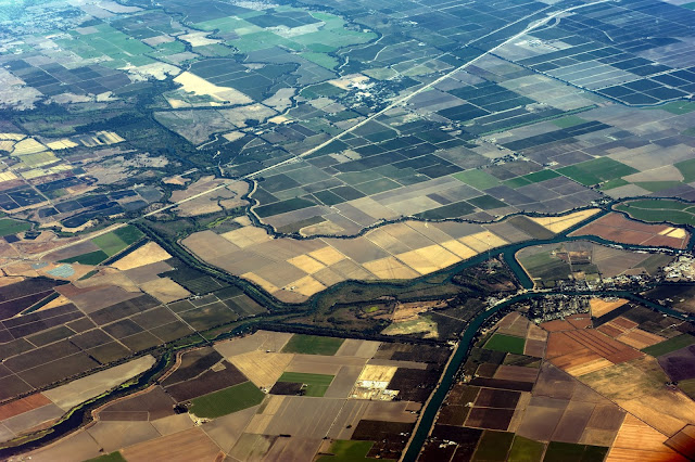 Photo from a plane showing towns, settlements and farm lands along a canal in the US.