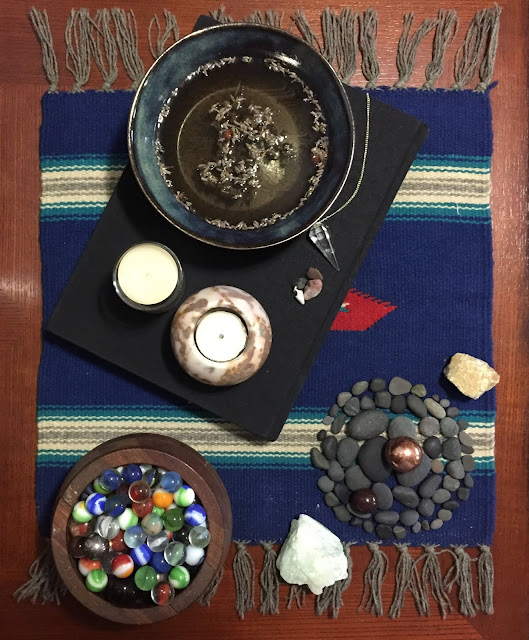 A black bowl of salt water, 2 white candles, a clear quartz pendulum, a black cloth-covered journal, black stones from the shore of Lake Huron, a bowl of marbles in a bowl made by my father, aquamarine, jasper and hematite sphere, copper sphere, and septarian
