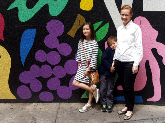 a photo of a woman and two children in front of a colourful wall mural