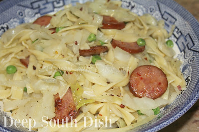 A dish of cabbage and onions pan sauteed in butter with cooked egg noodles and andouille sausage stirred in.