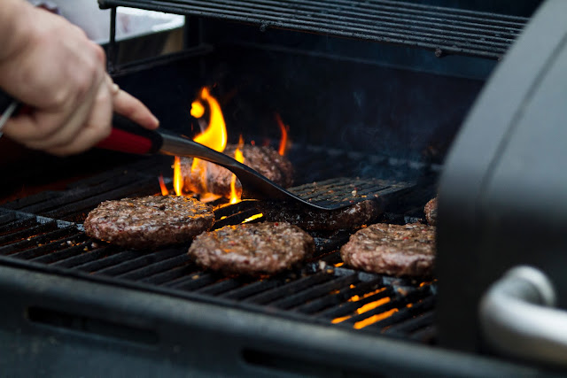 Person Grilling Hamburger Patties | Photo by Zac Cain via Unsplash