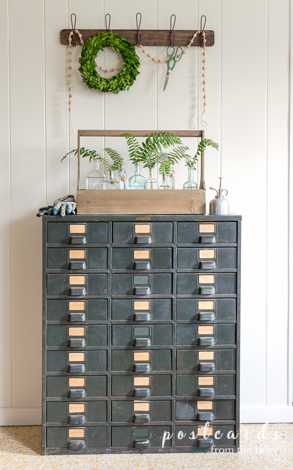 vintage metal industrial cabinet with wooden toolbox and fern branches in vintage glass bottles