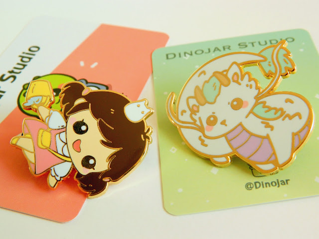 A photo showing two enamel pins of Studio Ghibli characters; Mei from My Neighbour Totoro and Dragon Haku from Spirited Away. Both are made by Dinojar Studio, and are very cute!
